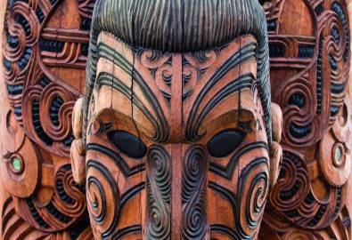 Close-up of a brown and black Maori carving of a man